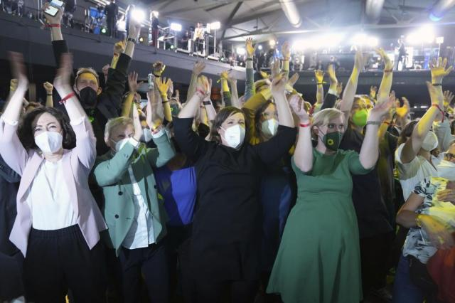 Guests at the election party of the Greens party react after the publication of the first forecasts on the outcome of the election for the state of Berlin, in Berlin, Sunday, Sept. 26, 2021. Exit polls show the center-left Social Democrats in a very close race with outgoing Chancellor Angela Merkel's bloc in Germany's parliamentary election, which will determine who succeeds the longtime leader after 16 years in power (Kay Nietfeld/dpa via AP)