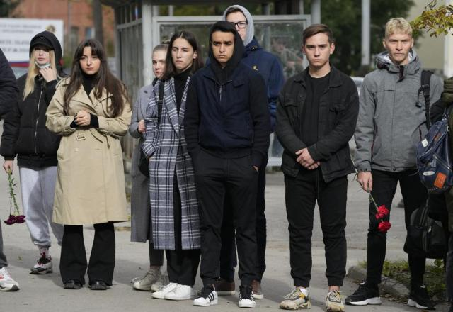 Students stand outside the Perm State University following a campus shooting in Perm, about 1,100 kilometers (700 miles) east of Moscow, Russia, Tuesday, Sept. 21, 2021. A student opened fire at the university, leaving a number of people dead and injured, before being shot in a crossfire with police and detained. Beyond saying that he was a student, authorities offered no further information on his identity or a possible motive. (AP Photo/Dmitri Lovetsky)