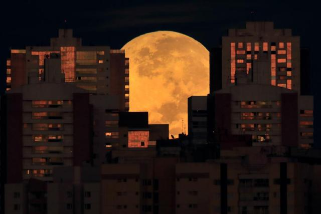 The moon is partially covered by buildings in Brasilia, Brazil, at the start of a total lunar eclipse early Wednesday, May 26, 2021. Wednesday's eclipse is the first in more than two years and coincides with a supermoon. (AP Photo/Eraldo Peres)