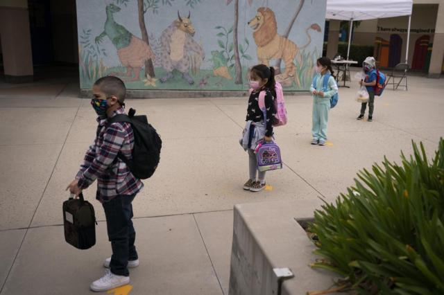 FILE - In this April 13, 2021, file photo, socially distanced kindergarten students wait for their parents to pick them up on the first day of in-person learning at Maurice Sendak Elementary School in Los Angeles. The number of Americans getting COVID-19 vaccine shots is nearing an average of 1 million per day. Demand is expected to spike in a few weeks when elementary school age children can begin getting vaccinated. (AP Photo/Jae C. Hong, File)