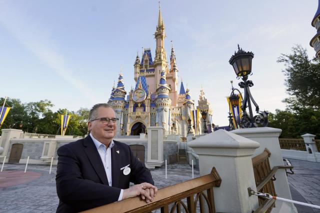 George Kalogridis, president of segment development and enrichment for Disney Parks, stands in front of the Cinderella Castle at the Magic Kingdom theme park at Walt Disney World Monday, Aug. 30, 2021, in Lake Buena Vista, Fla. Kalogridis was one of 6,000 employees that was working at the theme park on opening day in 1971. (AP Photo/John Raoux)