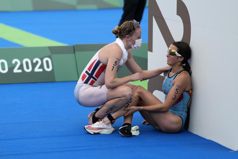 ARCHIVO - En esta foto de archivo del 27 de julio de 2021, Claire Michel de Bélgica es asistida por Lotte Miller de Noruega después del final de la competencia individual femenina de triatlón en los Juegos Olímpicos de Verano de 2020, en Tokio, Japón.  En unos Juegos Olímpicos extraordinarios donde la salud mental ha estado al frente y en el centro, los actos de bondad están en todas partes.  Se ha capturado a los atletas más competitivos del mundo mostrando amabilidad y calidez entre ellos, celebrando, animando, secándose las lágrimas de decepción de los demás.  (Foto AP / David Goldman, archivo)