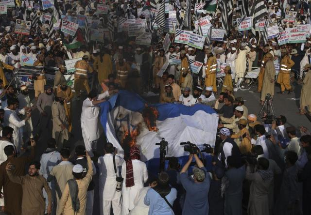 Supporters of the Pakistani religious group' Jamiat Ulema-e Islam burn a representation of an Israeli flag during a rally in support of Palestinians, in Peshawar, Pakistan, Friday, May 21, 2021. (AP Photo/Muhammad Sajjad)