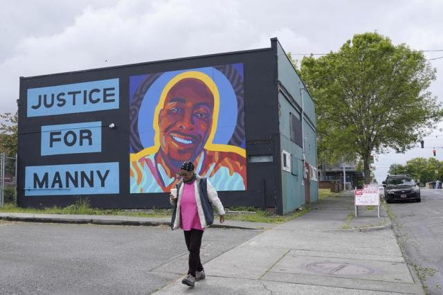 """A woman walks past a mural honoring Manuel """"Manny"""" Ellis, Thursday, May 27, 2021, in the Hilltop neighborhood of Tacoma, Wash., south of Seattle. Ellis died on March 3, 2020 after he was restrained by police officers. Earlier in the day Thursday, the Washington state attorney general filed criminal charges against three police officers in the death of Ellis, who told the Tacoma officers who were restraining him he couldn't breathe before he died. (AP Photo/Ted S. Warren)"""