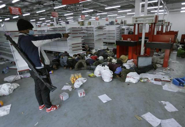 A security person aprehends looters inside a store in Vosloorus near Johannesburg, Tuesday July 13, 2021. South Africa's rioting continued Tuesday with the death toll rising to 32 as police and the military struggle to quell the violence in Gauteng and KwaZulu-Natal provinces. The violence started in various parts of KwaZulu-Natal last week when Zuma began serving a 15-month sentence for contempt of court. (AP Photo/Themba Hadebe)