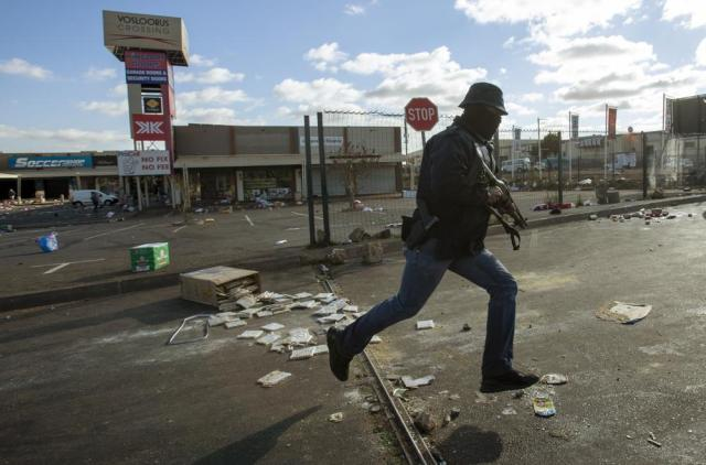 A metro officer dressed in plainclothes, pursues looters looters at a shopping centre in Soweto, Johannesburg, Tuesday July 13, 2021. South Africa's rioting continued Tuesday with the death toll rising to 32 as police and the military struggle to quell the violence in Gauteng and KwaZulu-Natal provinces. The violence started in various parts of KwaZulu-Natal last week when Zuma began serving a 15-month sentence for contempt of court. (AP Photo/Themba Hadebe)