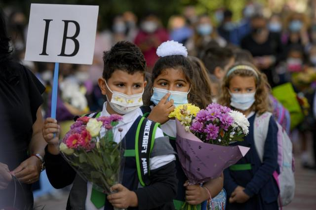 Children wearing face masks hold flowers during festivities marking the beginning of the school year at a school in Bucharest, Romania, Monday, Sept. 13, 2021. Children returned to classrooms in Romania, a country with one of the lowest COVID-19 vaccination rates in the European Union, as the daily infection numbers continue to rise. (AP Photo/Andreea Alexandru)