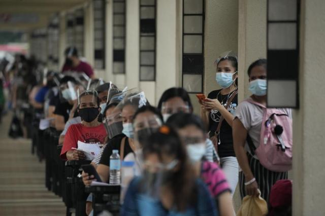 Residents wait for their turn at a vaccination center in Quezon city, Philippines on Monday, Sept. 13, 2021. The government continues to urge Filipinos to get vaccinated as COVID-19 cases keep rising in the country. (AP Photo/Aaron Favila)