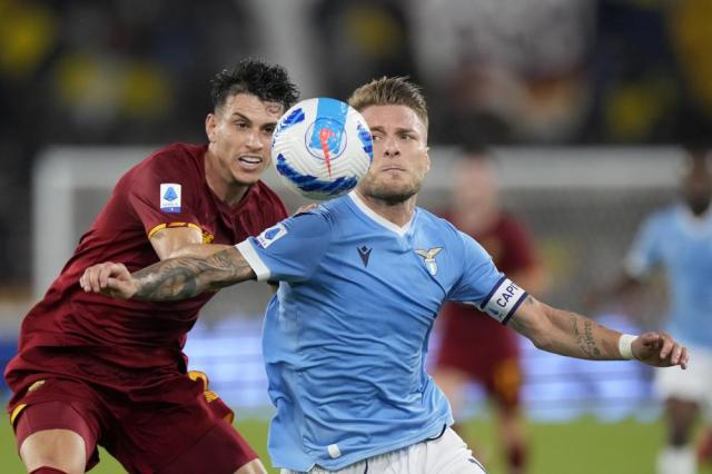 Lazio's Ciro Immobile shields the ball from Roma's Roger Ibanez, left, during a Serie A soccer match between Lazio and Roma, at Rome's Olympic Stadium, Sunday, Sept. 26, 2021. (AP Photo/Andrew Medichini)