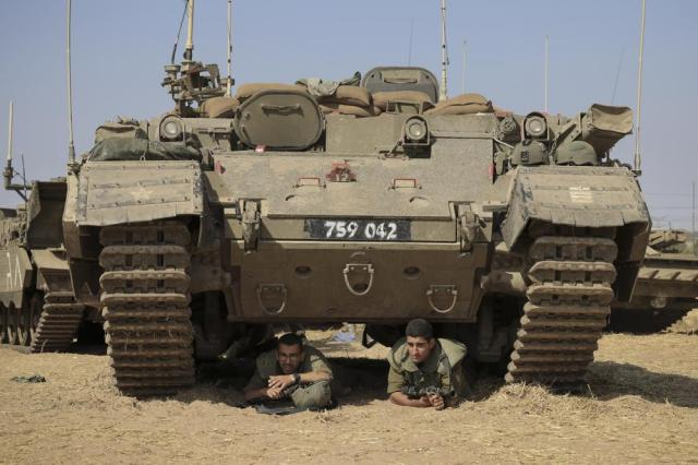 Israeli soldiers take cover under armored vehicles as a siren sounds warning of incoming rockets fired from Gaza strip in a staging ground near the Israeli-Gaza border southern Israel, Thursday, May 20, 2021. (AP Photo/Tsafrir Abayov)