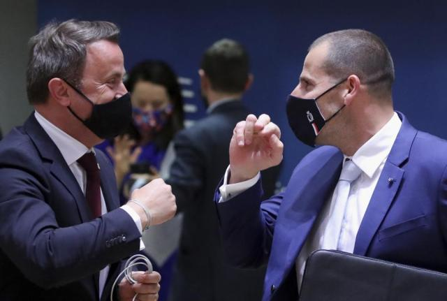 Luxembourg's Prime Minister Xavier Bettel, left, speaks with Malta's Prime Minister Robert Abela during a round table meeting at an EU summit in Brussels, Monday, May 24, 2021. European Union leaders are expected, during a two day in-person meeting, to focus on foreign relations, including Russia and the UK. (Yves Herman, Pool via AP)