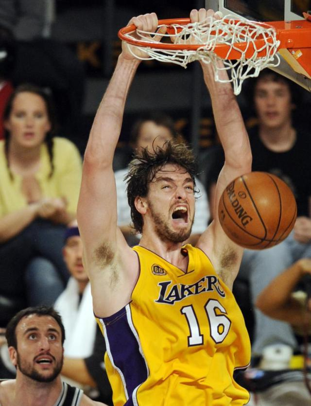 FILE - Los Angeles Lakers' Pau Gasol (16), of Spain, dunks as San Antonio Spurs' Manu Ginobili, left, of Argentina, looks on during the second half of Game 5 of the NBA Western Conference basketball finals in Los Angeles, in this Thursday, May 29, 2008, file photo. Pau Gasol announced his retirement from basketball on Tuesday,  Oct. 5, 2021, ending a career that lasted more than two decades and earned him two NBA titles and a world championship gold with Spain's national team. (AP Photo/Chris Pizzello, File)