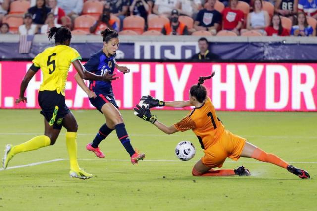 U.S. forward Carli Lloyd kicks the ball past Jamaica goalkeeper Chinyelu Asher (7) to score during the first half of their 2021 WNT Summer Series soccer match, Sunday, June 13, 2021, in Houston. (AP Photo/Michael Wyke)