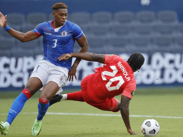 Canada forward Ayo Akinola (20) is knocked to the ground by Haiti defender Francois Dulysse (3) during the second half of a CONCACAF Gold Cup soccer match in Kansas City, Kan., Thursday, July 15, 2021. Dulysse was issued a red card. (AP Photo/Colin E. Braley)