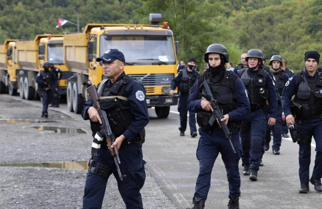 Kosovo police officers patrol by trucks where Kosovo Serbs block a road near the northern Kosovo border crossing of Jarinje, Monday, Sept. 20, 2021. Tensions soared Monday at the border between Kosovo and Serbia as Kosovo deployed additional police to implement a rule to remove Serbian license plates from cars entering Kosovo, while Serbs protested the move. (AP Photo/Bojan Slavkovic)