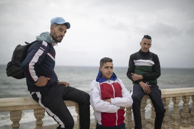 """Badreddine, left, 22, Salah, center, 22 and Hosam, 24, pose for a photo as they wait for a chance to cross to the Spanish enclave of Ceuta from the northern town of Fnideq, Morocco, Thursday, May 20, 2021. An extraordinary surge of migrants seeking to leave Morocco for Spain this week has left the border town suffering under the strain. """"We will keep trying. We will find one way or another, even if the ocean turns into ice!"""" said 27-year-old Badreddine. (AP Photo/Mosa'ab Elshamy)"""