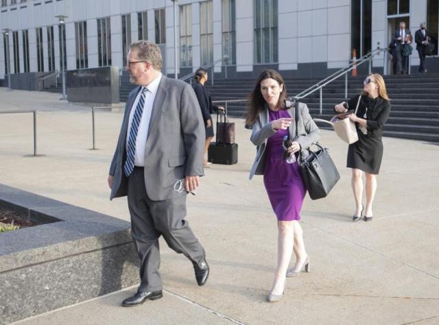Attorneys and staff associated with a federal trial of pharmacies, CVS, Walgreens, Giant Eagle and Walmart, leave the Carl B. Stokes Federal Courthouse in Cleveland, Monday, Oct. 4, 2021. The pharmacies are being sued by Ohio counties Lake and Trumbull for their part in the opioid crisis. (AP Photo/Phil Long)