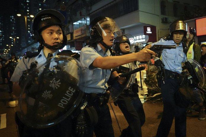 Policías sacan sus armas después de una confrontación con manifestantes durante una protesta en Hong Kong el 25 de agosto. | Associated Press