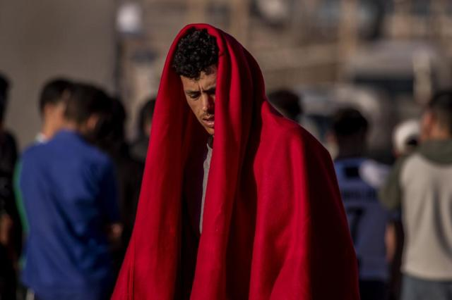 A migrant waits at the Spanish enclave of Ceuta, near the border of Morocco and Spain, Wednesday, May 19, 2021. Spanish officials are acknowledging for the first time that the unprecedented migrant crisis has been triggered by an angry Rabat at Madrid's decision to provide medical treatment to the militant boss of the Polisario Front. (AP Photo/Bernat Armangue)
