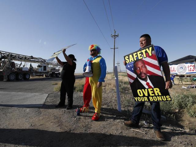 Mayor Rolando Castro, far right, holds a protest sign with a photo of Douglas K. White, warden at the Federal Correctional Institution at Mendota, as fellow protester Paul Millan, dressed as a clown, looks on during a demonstration against staffing shortages, near the prison entrance in Mendota, Calif., Monday, May 17, 2021. (AP Photo/Gary Kazanjian)