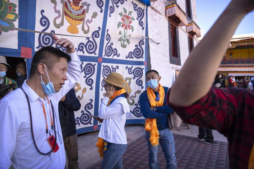 Tourists use earpieces to listen to a lecture at the Potala Palace in Lhasa in western China's Tibet Autonomous Region, Tuesday, June 1, 2021. Tourism is booming in Tibet as more Chinese travel in-country because of the coronavirus pandemic, posing risks to the region's fragile environment and historic sites. (AP Photo/Mark Schiefelbein)