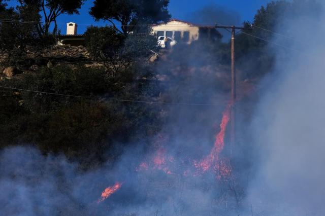 A wildfire burns near a home Wednesday, Oct. 13, 2021, in Goleta, Calif. A wildfire raging through Southern California coastal mountains threatened ranches and rural homes and kept a major highway shut down Wednesday as the fire-scarred state faced a new round of dry winds that raise risk of flames. The Alisal Fire covered more than 22 square miles (57 square kilometers) in the Santa Ynez Mountains west of Santa Barbara. (AP Photo/Ringo H.W. Chiu)