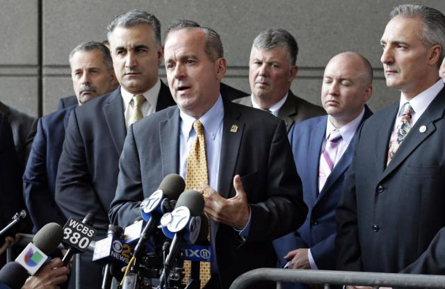 FILE — In this May 31, 2017, file photo, Sgt. Ed Mullins, the head of the Sergeants Benevolent Association, center, speaks to the media outside of the Bronx Supreme Court in the Bronx borough of New York. Federal agents on Tuesday, Oct. 5, 2021, raided the offices of a New York City police union, the Sergeants Benevolent Association, and the Long Island home of its bombastic leader, Ed Mullins, who has clashed repeatedly with city officials over his incendiary tweets and hard-line tactics. (AP Photo/Frank Franklin II, File)