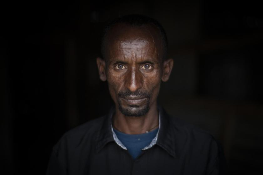 """Tedros Abadi, 38, originally from Samre, Ethiopia, is photographed at a reception center for the internally-displaced in Mekele, in the Tigray region of northern Ethiopia Sunday, May 9, 2021. The former shopkeeper says Eritrean troops arrived in his village as recently as April. After being ambushed by Tigrayan guerrillas, they gunned down priests walking home after service on a Sunday afternoon and burned about 20 houses, he recalls. """"Nothing is left there,"""" said Tedros, who does not know where his family is. """"I left home because they were targeting all civilians, not only priests."""" (AP Photo/Ben Curtis)"""