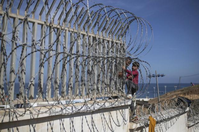 A boy is helped by a man while climbing a fence in the area at the border of Morocco and Spain, outside the Spanish enclave of Ceuta, Tuesday, May 18, 2021. (AP Photo/Mosa'ab Elshamy)