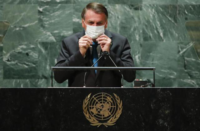 Brazil's President Jair Bolsonaro puts back on a protective face mask after speaking during the 76th Session of the United Nations General Assembly at U.N. headquarters in New York on Tuesday, Sept. 21, 2021.  (Eduardo Munoz/Pool Photo via AP)