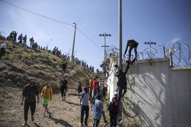 FILE - In this May 18, 2021, file photo, people climb a fence in the area at the Spain-Morocco border, outside the Spanish enclave of Ceuta. Thousands of would-be migrants converged on the Moroccan border town of Fnideq this week, part of an extraordinary mass effort to swim or scale barbed-wire fences to get into Spain for a chance at a new life. (AP Photo/Mosa'ab Elshamy)