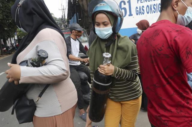 A woman carries her oxygen tank after having it refilled at a recharging station in Jakarta, Indonesia, Friday, July 9, 2021. The world's fourth most populous country is running out of oxygen as it endures a devastating wave of coronavirus cases and the government is seeking emergency supplies from other countries, including Singapore and China. (AP Photo/Tatan Syuflana)