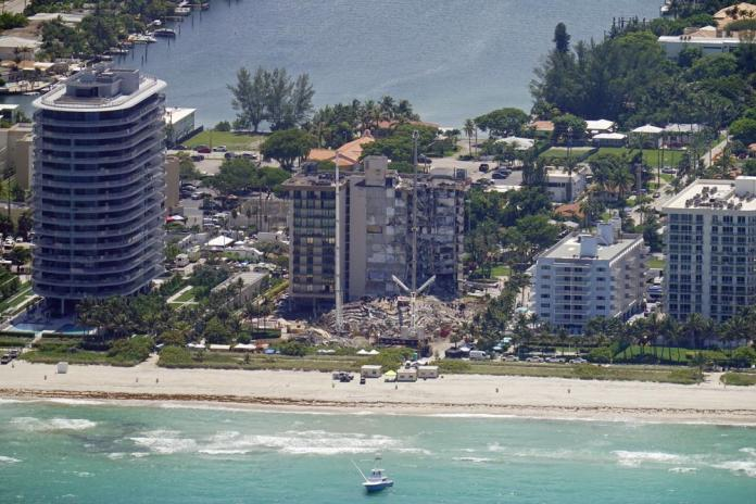 This aerial image shows an oceanfront condo building that partially collapsed three days earlier, resulting in fatalities and many people still unaccounted for, in Surfside, Fla., Sunday, June 27, 2021. (AP Photo/Gerald Herbert)