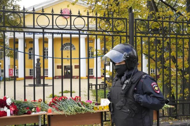 A police officer walks past flowers and candles displayed on a table outside the Perm State University following a campus shooting in Perm, about 1,100 kilometers (700 miles) east of Moscow, Russia, Tuesday, Sept. 21, 2021. A student opened fire at the university, leaving a number of people dead and injured, before being shot in a crossfire with police and detained. Beyond saying that he was a student, authorities offered no further information on his identity or a possible motive. (AP Photo/Dmitri Lovetsky)