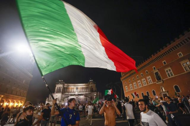 Italy's fans celebrate in Rome, Monday, July 12, 2021, after Italy beat England to win the Euro 2020 soccer championships in a final played at Wembley stadium in London. Italy beat England 3-2 in a penalty shootout after a 1-1 draw. (AP Photo/Riccardo De Luca)
