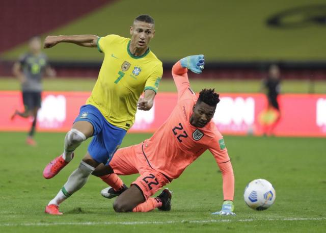 Brazil's Richarlison, left, and Ecuador's goalkeeper Alexander Dominguez eye the ball during a qualifying soccer match for the FIFA World Cup Qatar 2022 at Beira-Rio stadium in Porto Alegre, Brazil, Friday, June 4, 2021. (AP Photo/Andre Penner)