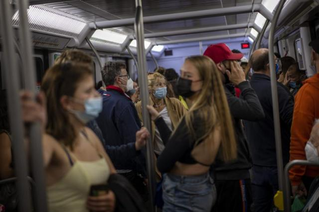 Commuters wearing face masks to protect against the spread of Coronavirus travel by train in Barcelona, Spain, Saturday, May 15, 2021. (AP Photo/Emilio Morenatti)