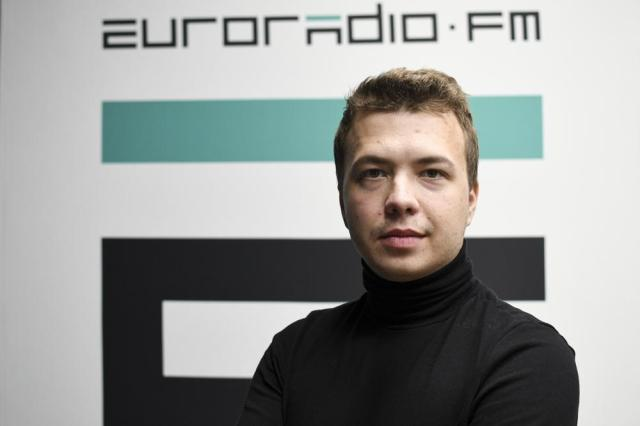 In this handout photo released by European Radio for Belarus, Belarus journalist Raman Pratasevich poses for a photo in front of euroradio.fm sign in Minsk, Belarus, Sunday, Nov. 17, 2019. Western outrage grew and the European Union threatened more sanctions Monday over the forced diversion of a plane to Belarus in order to arrest an opposition journalist. The dramatic gambit apparently ordered by the country's authoritarian president to suppress dissent was denounced as piracy, a hijacking and terrorism. (Euroradio via AP)