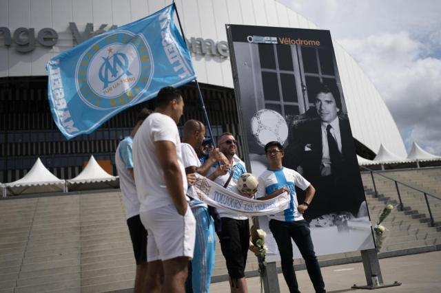 People gather outside the Orange Velodrome stadium in Marseille, southern France, Sunday, Oct. 3, 2021. Bernard Tapie, the charismatic president of French soccer club Marseille during its glory era whose reign was marred by a match-fixing scandal, has died, Sunday Oct. 3, 2021. He was 78. (AP Photo/Daniel Cole)