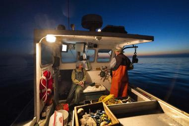 Virginia Oliver, left, chats with her son Max Oliver while heading out to sea to fish for lobster at dawn, Tuesday, Aug. 31, 2021, off Rockland, Maine. Virginia Oliver, age 101, is the state's oldest lobster fisher. (AP Photo/Robert F. Bukaty)