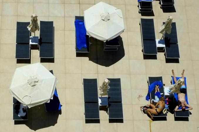 FILE - In this May 22, 2021, file photo, a family on vacations lounges at the pool of Nissi Blue hotel in southeast resort of Ayia Napa, in the eastern Mediterranean island of Cyprus. Coronavirus infections, hospitalizations and deaths are plummeting across much of Europe. Italy and Cyprus are due to let restaurants reopen for indoor dining June 1, with discos — a big summertime moneymaker for southern European beach resorts — scheduled soon thereafter. (AP Photo/Petros Karadjias)