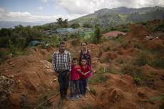 Eleuterio Esquivel, de 51 años, a la izquierda, posa para una fotografía junto con su esposa Elsa Mejía, de 40, y sus gemelos Ibis y Noel Esquivel, de 7, en el sitio donde estuvo su casa antes de quedar destruída por un deslave provocado por el paso de los huracanes Eta e Iota en la comunidad de La Reina, Honduras, el miércoles 23 de junio de 2021. (AP Foto/Rodrigo Abd)
