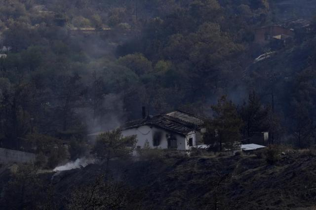 """A burned house in Ora village, in Larnaca mountain region, Cyprus, Sunday, July 4, 2021. Cyprus' interior minister says four people have died in what he called the """"most destructive"""" fire in the island nation's history. (AP Photo/Petros Karadjias)"""