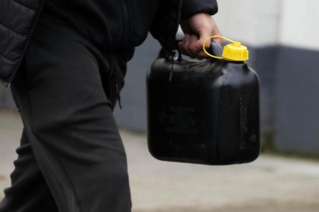 A man carries a filled up petrol canister at a petrol station in London, Thursday, Sept. 30, 2021. Many gas stations around Britain have shut down in the past five days after running out of fuel, a situation exacerbated by panic buying among some motorists. Long lines of vehicles formed at pumps that were still open, blocking roads and causing traffic chaos. Some drivers have had to endure hourslong waits to fill up. (AP Photo/Frank Augstein)
