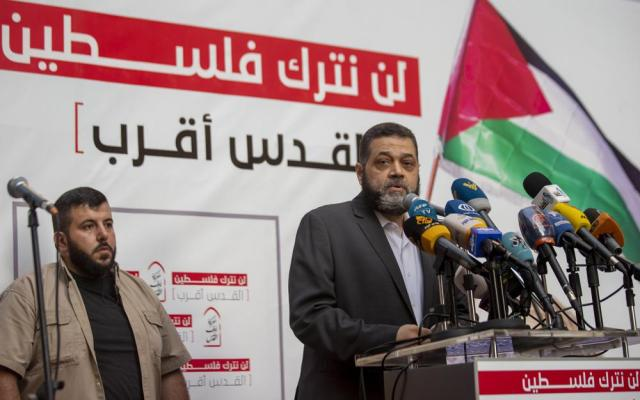 """Senior Hamas official Osama Hamdan speaks during a rally organized by Lebanon's militant Hezbollah group to express solidarity with the Palestinian people, in the southern suburb of Beirut, Lebanon, Monday, May 17, 2021. Hamdan said in an interview Thursday, May 20,  that he expects a cease-fire between the group's Gaza branch and Israel within 24 hours, but warned that Hamas has """"no shortage of missiles."""" Arabic reads, """"We will not leave Palestine"""". (AP Photo/Hassan Ammar)"""