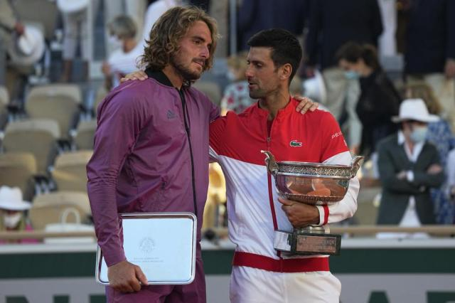 Serbia's Novak Djokovic ,right, and Stefanos Tsitsipas of Greece hold their trophies after their final match of the French Open tennis tournament at the Roland Garros stadium Sunday, June 13, 2021 in Paris. Djokovic won 6-7 (6), 2-6, 6-3, 6-2, 6-4. (AP Photo/Michel Euler)