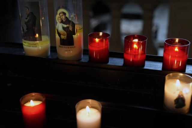 Candles decorate with Saint Anthony are lighten in a Catholic Church in central Paris, Tuesday, Oct. 5, 2021. The head of France's Catholic bishops conference is asking forgiveness from the estimated 330,000 victims of child sex abuse by the church found in a groundbreaking report. The report was released Tuesday after extensive research in France's first major reckoning with the issue. (AP Photo/Francois Mori)