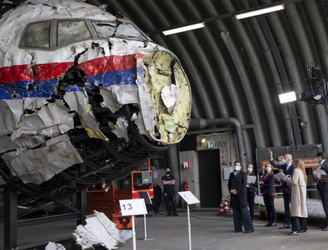Presiding judge Hendrik Steenhuis, right, points as he and other trial judges and lawyers view the reconstructed wreckage of Malaysia Airlines Flight MH17, at the Gilze-Rijen military airbase, southern Netherlands, Wednesday, May 26, 2021. (AP Photo/Peter Dejong, Pool)