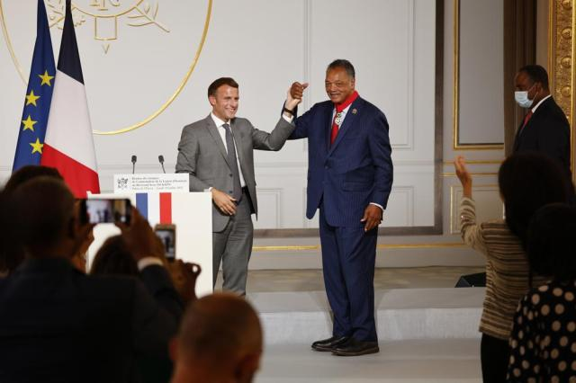 French President Emmanuel Macron, left, and Reverend Jesse Jackson raise their hands after Jackson was awarded with the Legion d'Honneur (Officer of the Legion of Honor) medal during a ceremony at the Elysee Palace in Paris, Monday, July 19, 2021. (Ludovic Marin/Pool Photo via AP)