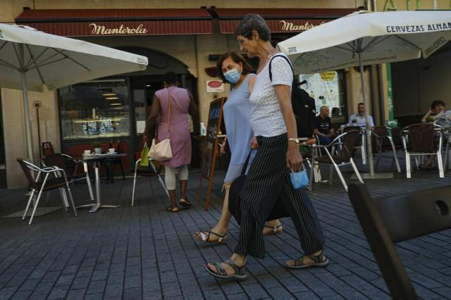 Two women walk past customers in a bar in Pamplona, northern Spain, Monday, July 5, 2021. (AP Photo/Alvaro Barrientos)